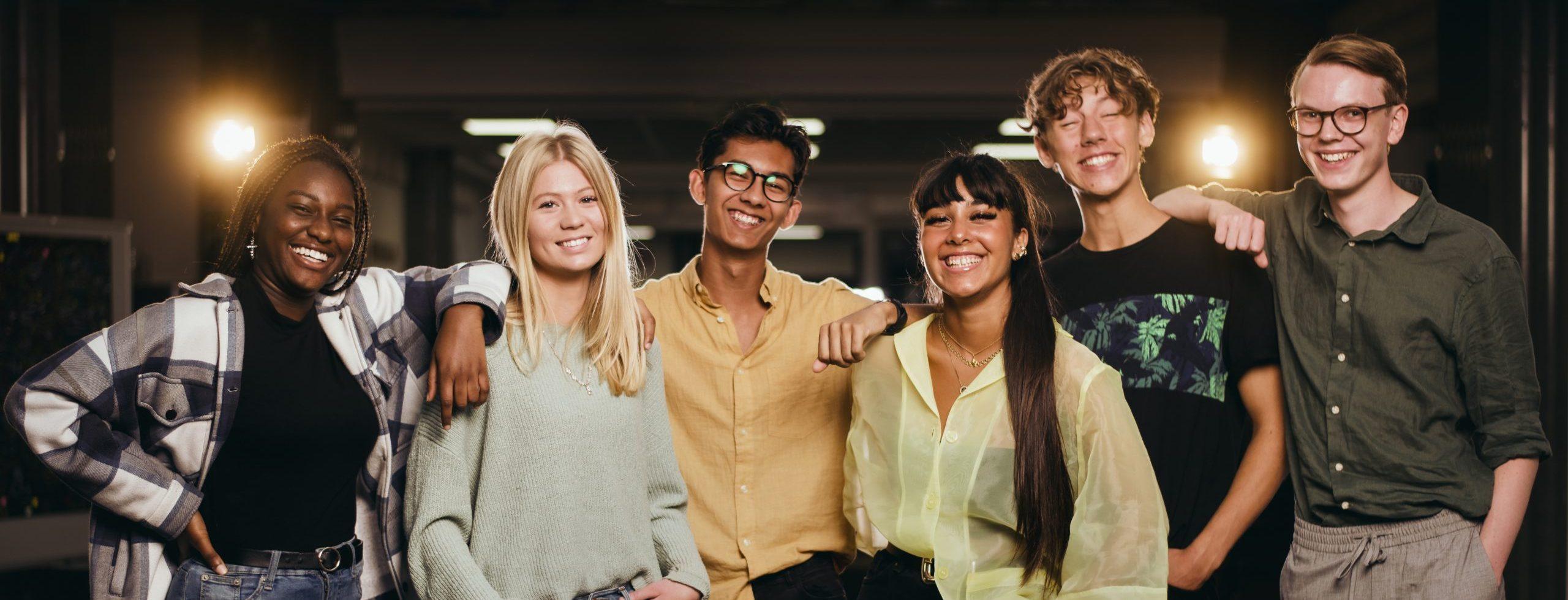 Sju elever står och håller armarna om varandra och kollar glatt in i kameran.