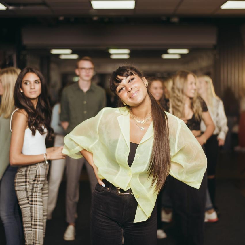Elever står och håller armarna om varandra och kollar glatt in i kameran.